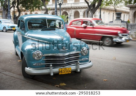 HAVANA, CUBA - JUNE, 2011: Vintage American taxi cars share the road on the Paseo del Prado in Central Havana.