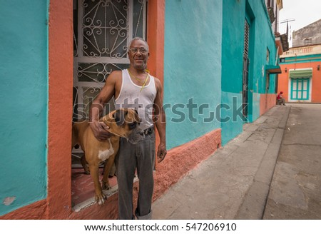 HAVANA, CUBA - March 20, 2016.  Cuban man with his boxer in Havana, Cuba