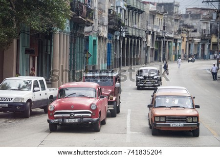 HAVANA, CUBA- MARCH 4, 2016: Old vintage cars driving in the capital city. The island is known for the diversity of vintage cars still driving. They have become a tourist attraction