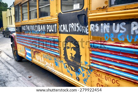 HAVANA, CUBA - MARCH 22, 2015 - school bus on Havana street, covered with political messages urging the freeing of 5 political prisoners that were held in the US. - stock photo