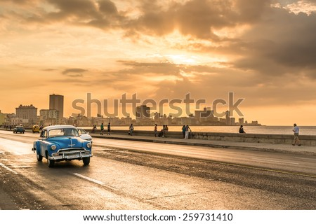 HAVANA,CUBA - MARCH 5, 2014 : Vintage american car at the Malecon avenue during a beautiful sunset - stock photo