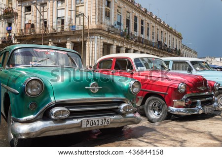 Havana, Cuba - May 28, 2014: Green and red classic cars parked in the streets of Old Havana