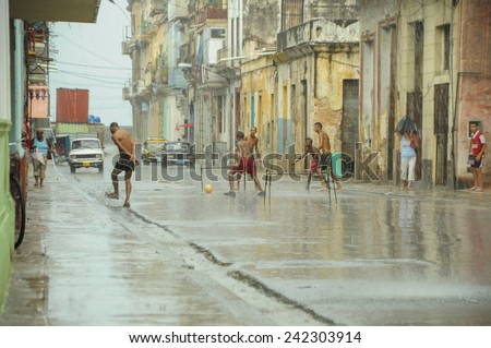 HAVANA, CUBA - MAY 31, 2013 Local Cuban kids play football or soccer on street in Havana, Cuba while tropical storm approching with heavy rain but very hot air. - stock photo