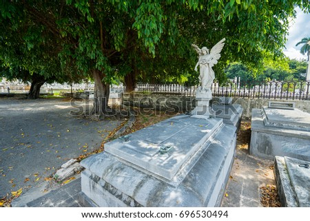 HAVANA, CUBA - MAY 11, 2017: The beautiful stone sculptures of sacred angel. The work of art, family crypt at the public cemetery in Havana center in hot sunny summer day