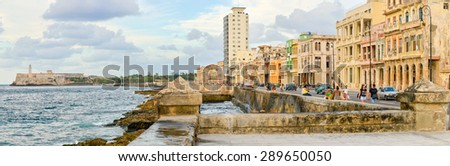 HAVANA,CUBA - MAY 3:2015 : The Malecon seawall in Havana with a view of old buildings, people and old cars - stock photo