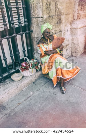 HAVANA, CUBA - MAY 15, 2016: Woman in traditional Cuban dress, posing with a cigar on the streets of Havana, Cuba.