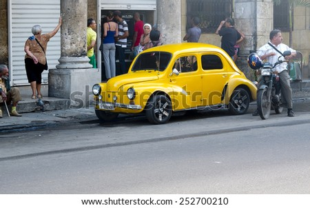 HAVANA, CUBA - NOVEMBER 21:  A french vintage yellow car parked along a sidewalk in the center of the town ,on november 21, 2014, in Havana, Cuba  - stock photo