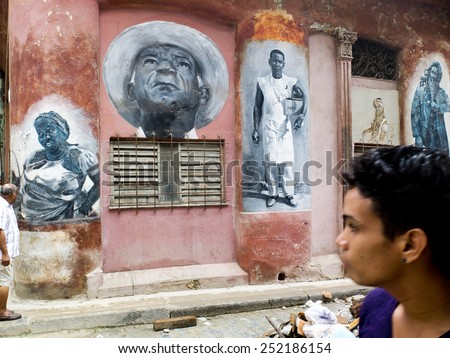 HAVANA, CUBA - NOVEMBER 23: passersby look at portraits painted on a wall of the center of the city, on november 23, 2014, in Havana, Cuba. - stock photo
