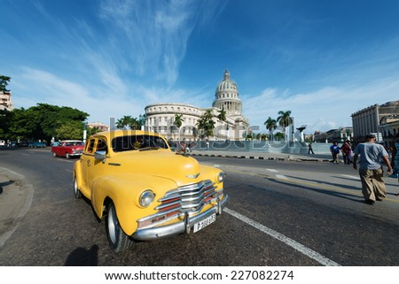 HAVANA, CUBA - OCTOBER 8, 2014: Old classic American yellow car rides in front of the Capitol. Before a new law issued on October 2011, Cubans could only trade cars that were on the road before 1959.  - stock photo