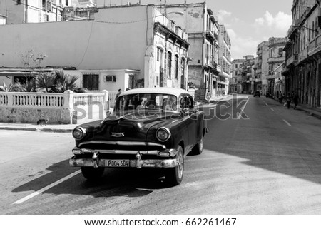 HAVANA,CUBA-OCTOBER 13:People and old car on streets of Havana October 13,2015 in Havana. With 2.4 mil. inhabitants in the city and 3.7 in its urban area, Havana is the largest city in the Caribbean