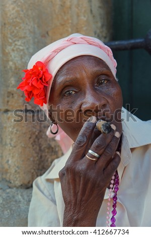 Havana, CUBA - 28 OCTOBER 2012: Portrait of african cuban woman smoking cigar in Havana, Cuba. - stock photo