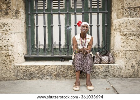 HAVANA,CUBA-OCTOBER 14:Woman smoking cigar on streets of Havana October 14,2015 in Havana. With 2.4 mil. inhabitants in the city and 3.7 in its urban area, Havana is the largest city in the Caribbean - stock photo