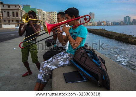 Havana, Cuba - September 25, 2015: Group of friends play music at sunset at Malecon in Havana, Cuba. Music is very common hobby in Cuba but also way to earn extra cash. - stock photo