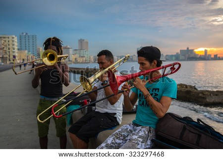 Havana, Cuba - September 25, 2015: Group of friends play music at sunset at Malecon. Music is very common hobby in Cuba but also way to earn extra cash. - stock photo