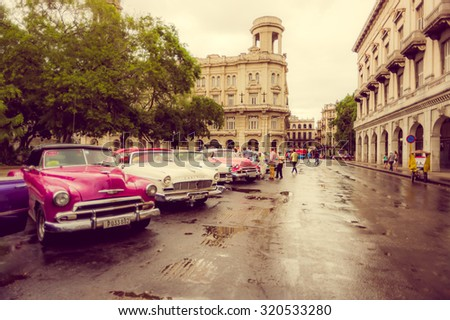 HAVANA, CUBA - SEPTEMBER 4, 2015: Old classic American cars rides in front of the Capitol. Before a new law issued on October 2011, cubans could only trade cars that were on the road before 1959. - stock photo