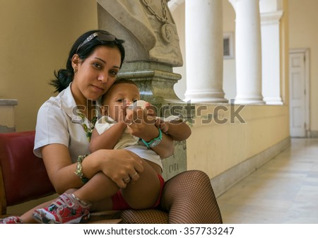 Havana, Cuba - 7 September 2015: Young mother and her child, working at the Museum of the Revolution in Havana, Cuba.