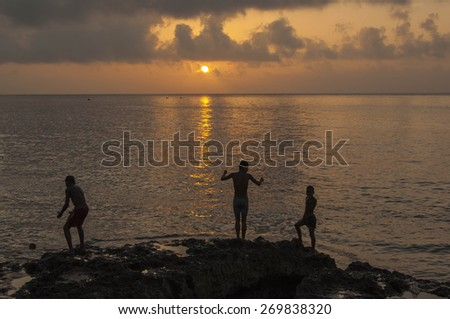 HAVANA/CUBA 4TH JULY 2006 - Kids playing on the Malecon at Sunset - stock photo