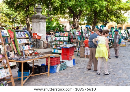 HAVANA-DECEMBER 20:Tourists visiting a street market December 20,2011 in Havana.With more than 2 million visitors a year,tourism has become a major source of income for many residents of the island - stock photo