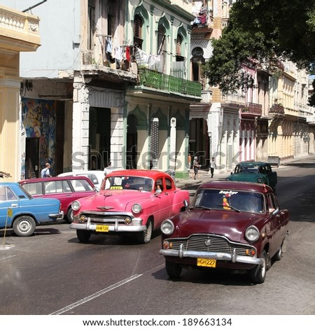 HAVANA - FEBRUARY 27: Classic American cars in the street on February 27, 2011 in Havana, Cuba. Cuba has one of the lowest car-per-capita rates (38 per 1000 people in 2008).  - stock photo