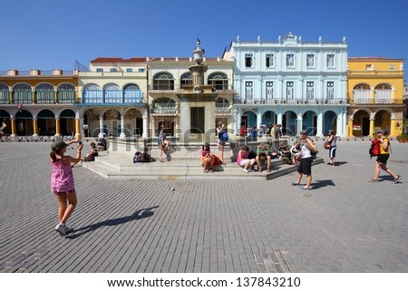 HAVANA - FEBRUARY 27: Tourists visit Old Town's Plaza Vieja on February 27, 2011 in Havana. Havana's Old Town is a UNESCO World Heritage Site and is Cuba's most visited area. - stock photo