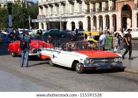 HAVANA - JANUARY 30: Cubans drive Classic American cars on January 30, 2011 in Havana. Recent change in law allows the Cubans to trade cars again. Most cars in Cuba are very old because of the old law - stock photo