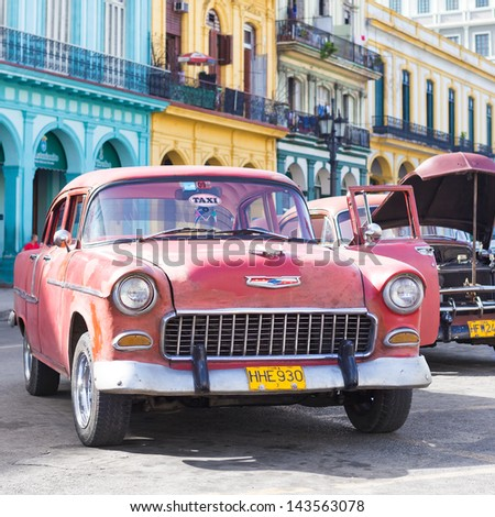HAVANA-JUNE 21:Old Chevy next to colorful buildings on June 21, 2013 in Havana. Before a new law issued on October 2011, cubans could only trade cars that were on the road before 1959 - stock photo