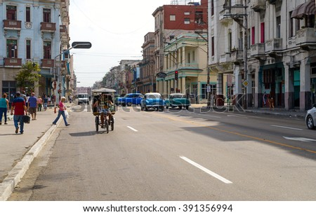 HAVANA - MARCH 7: Pedestrians and cars on one of the main streets in New Havana section, west of Prado Boulevard on March 7, 2016. - stock photo