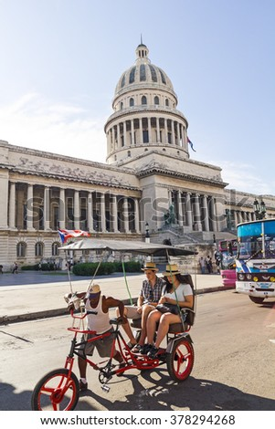 HAVANA-SEP 7: A car-bike with tourists circle in front of the Capitol on September 7 2011 in Havana, Cuba. The National Capitol Building was the seat of government in Cuba until the revolution in 1959 - stock photo
