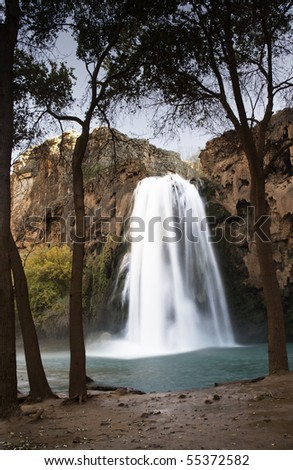 Havasu waters fall into the blue-green Havasupai Indian Reservation stream that flows to the Colorado River in Arizona's Grand Canyon. - stock photo