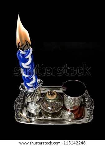 Havdala candle, kiddush cup, and spice set. The candle is lit after the conclusion of the Jewish sabbath; wine is served and a sweet spice is smelled. Isolated on a black background. - stock photo