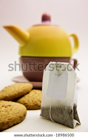 Have a break: a colorful tea set and a teabag on a pink background. - stock photo