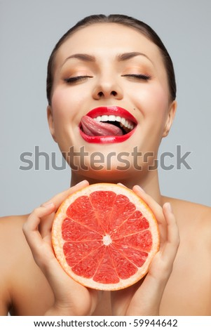 Have a lick. Pretty woman with delicious grapefruit in her arms.