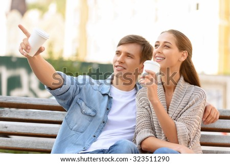 Have a look. Pleasant loving young couple sitting on the bench and drinking coffee while looking up
