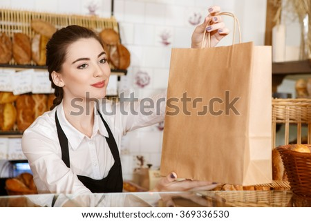 Have a nice day! Horizontal portrait of a gorgeous female baker passing paper bag with bread to the customer - stock photo