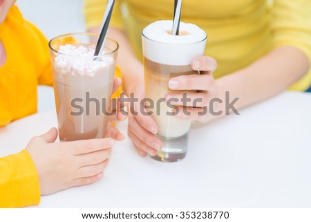 Have a rest. Close up of coffee standing on the table while mother and daughter drinking it while resting in the cafe - stock photo