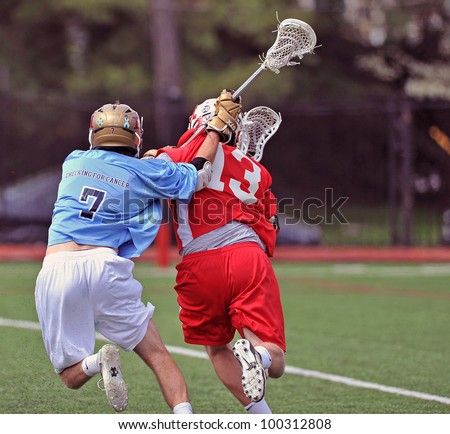 HAVERFORD, PA - APRIL 14: A player for the Haverford (PA) HS lacrosse team (#7) plays defense behind the net in the Checking for Cancer Invitational on April 14, 2012 in Haverford, PA. - stock photo