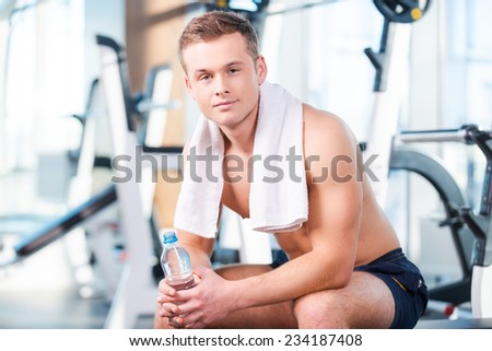Having a break after workout. Handsome young muscular man holding bottle with water and looking at camera while having a rest in gym - stock photo