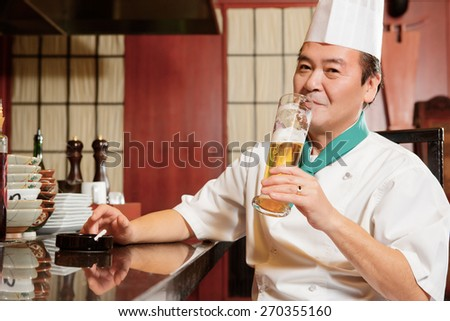 Having a break. Joyful Asian cook tasting beer sitting at the counter of restaurant kitchen - stock photo