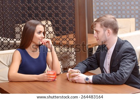 Having a date. Young beautiful couple sitting at the table in the bar and having some drinks - stock photo