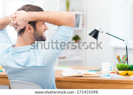 Having a minute break. Rear view of handsome young man in shirt holding hands behind head and smiling while sitting at his working place - stock photo