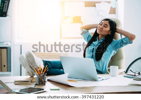 Having a nice break. Beautiful young Asian woman keeping hands behind head and looking relaxed while sitting at her working place - stock photo