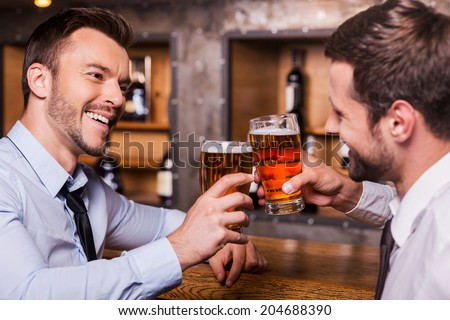 Having a pint with friend. Two cheerful young men in shirt and tie toasting with beer while sitting together at the bar counter  - stock photo