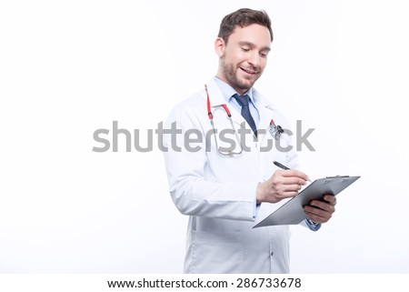 Having brisk mood. Handsome doctor holding folder and filling papers while keeping his eyes down - stock photo