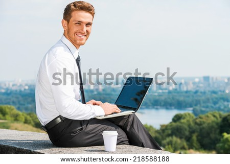 Having freedom to work everywhere. Confident young man in shirt and tie working on laptop and smiling while sitting outdoors with cityscape in the background - stock photo