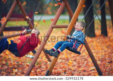Having fun in the playground / Autumn photo about boy and his grandmother with custom white balance, color filters, and vignette effect. - stock photo