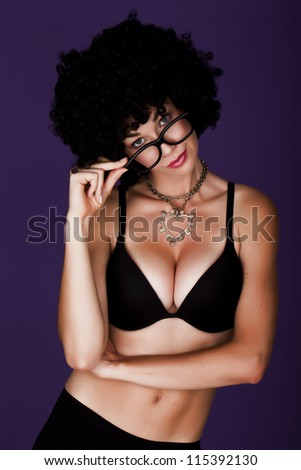 Having fun. Playful and funny woman wearing a curly wig on a purple background holding a mirror ball. - stock photo