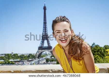 Having fun time near the world famous landmark in Paris. Portrait of smiling young woman in bright blouse against Eiffel tower