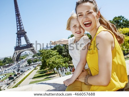 Having fun time near the world famous landmark in Paris. smiling mother and daughter travellers pointing on something in Paris, France