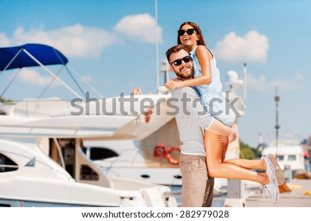 Having fun together. Cheerful young man picking up his beautiful girlfriendwhile standing on quay  - stock photo