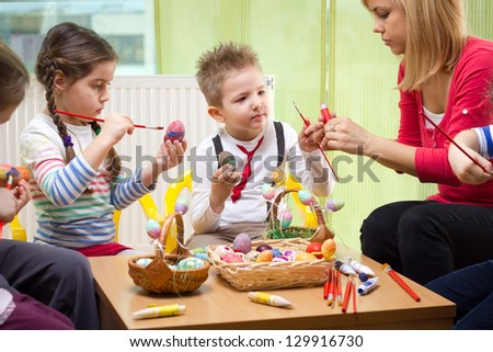 Having fun while painting easter eggs - stock photo